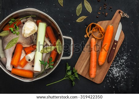 Preparing chicken stock with vegetables (bouillon) in a pot. Black chalkboard as background. Kitchen worktop scenery from above.