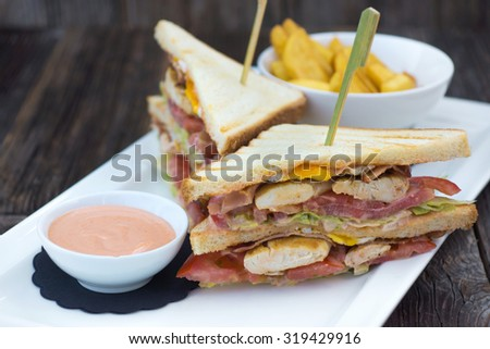 Club sandwich on toasted, served with crispy golden potato French fries  #319429916