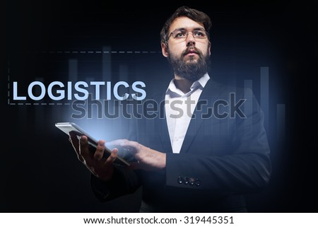 """Businessman holding a tablet pc with """"Logistics"""" text on virtual screen. Business concept. #319445351"""