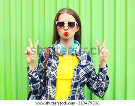 Fashion pretty cool girl wearing a sunglasses and headphones having fun over green background #319479506