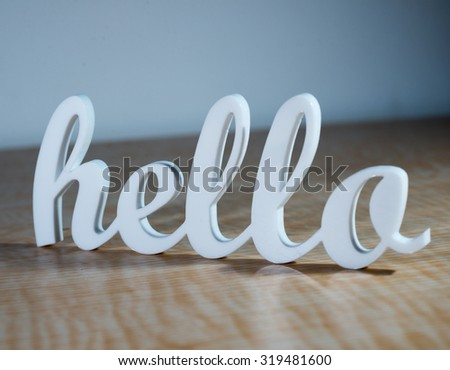 Cursive Hello Sign on Wooden Table.