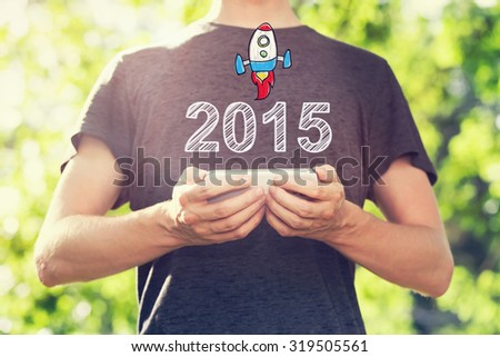 2015 concept with young man holding his smartphone outside in the park toward sunset