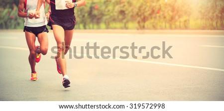 Marathon runners running on city road Royalty-Free Stock Photo #319572998
