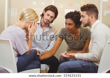 Colleagues supporting tensed businessman in creative office #319631531