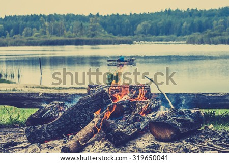 Rustic bonfire by the lake in the forest on the background of blurry boat with fisherman on the lake, vintage photo.