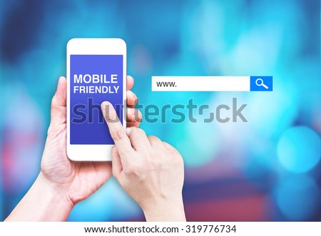 Hand touch mobile phone with  mobile friendly word with search box at blurred blue background, Digital marketing business concept #319776734