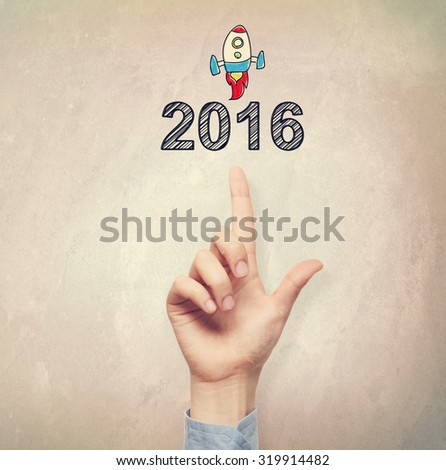 Hand pointing to 2016 concept on light brown wall background