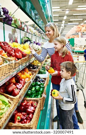 Mother and children with bell pepper in vegetables department in the supermarket #320007491