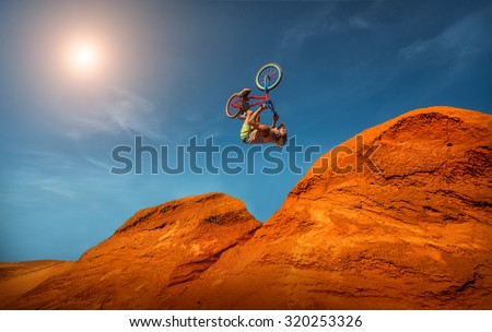 Biker rides on road in the high mountains of sand dunes . Background blue sky with clouds Royalty-Free Stock Photo #320253326