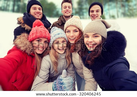 winter, technology, friendship and people concept - group of smiling men and women taking selfie and showing thumbs up outdoors #320406245