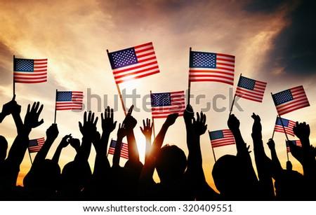 Group of People Waving American Flags in Back Lit