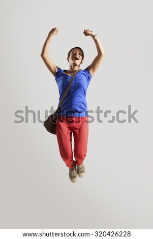 Portrait of young woman jumping #320426228