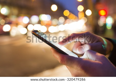 Man using his Mobile Phone in the street, night light bokeh Background #320479286