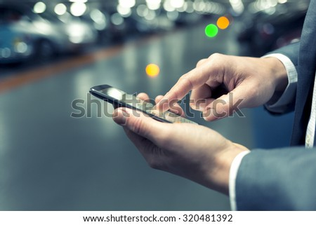 In parking car a man using his mobile phone. Light bokeh background. Filter vintage Royalty-Free Stock Photo #320481392