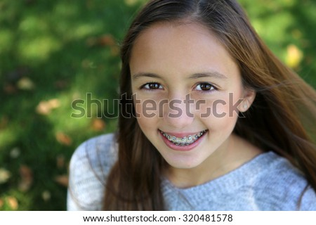 pretty girl with big brown eyes, long brown hair with braces #320481578