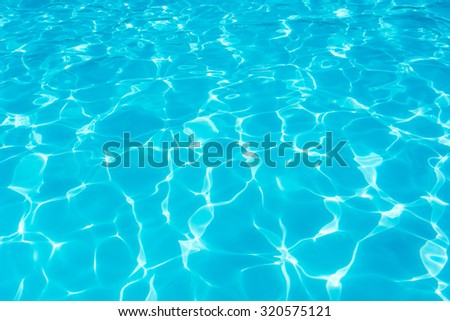 Swimming pool blue water reflecting the sun rippled details. #320575121