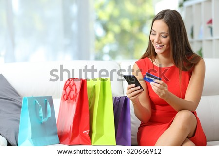 Fashion girl buying online with smart phone and credit card with colorful shopping bags beside #320666912