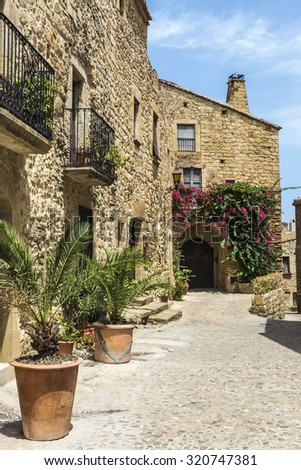 Medieval street with a tower defense in Pals, Girona, Catalonia, Spain #320747381