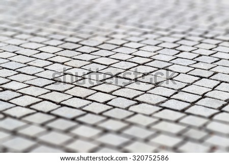 Close-up view of road with light grey square shape paving stone and blurred sides of picture