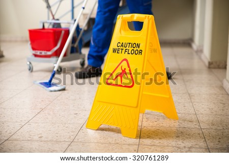Low Section Of Worker Mopping Floor With Wet Floor Caution Sign On Floor Royalty-Free Stock Photo #320761289