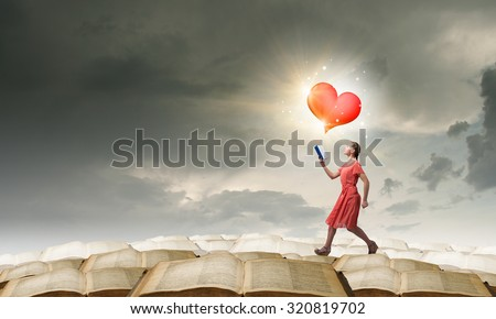 Young woman in red dress running with book in hand #320819702