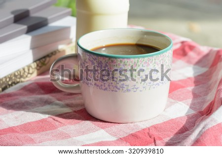 Coffee cup on plaid fabric at outdoor table #320939810