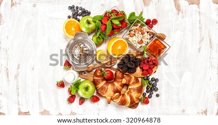 Breakfast with croissants, muesli, fresh berries, fruits orange, apple, milk. Healthy food concept. Top view #320964878