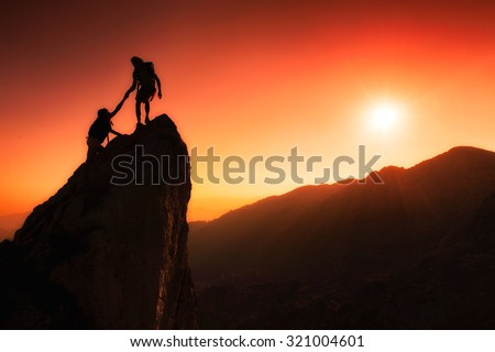 Team of climbers help to conquer the summit in teamwork in a fantastic mountain landscape at sunset #321004601