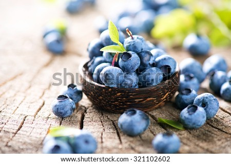 Freshly picked blueberries in wooden bowl. Juicy and fresh blueberries with green leaves on rustic table. Bilberry on wooden Background. Blueberry antioxidant. Concept for healthy eating and nutrition #321102602