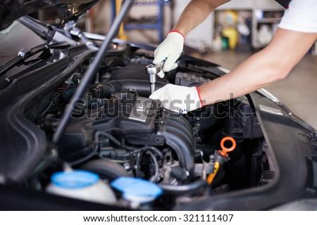 Hands of car mechanic in auto repair service. #321111407