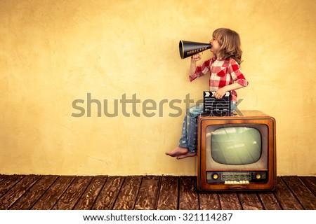 Kid shouting through vintage megaphone. Communication concept. Retro TV Royalty-Free Stock Photo #321114287
