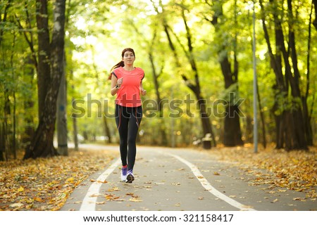 young fitness woman running at forest trail in park #321158417