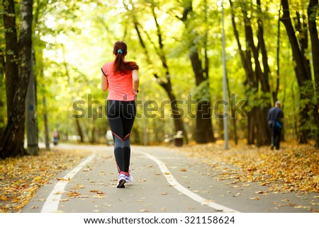 young fitness woman running at forest trail in park #321158624