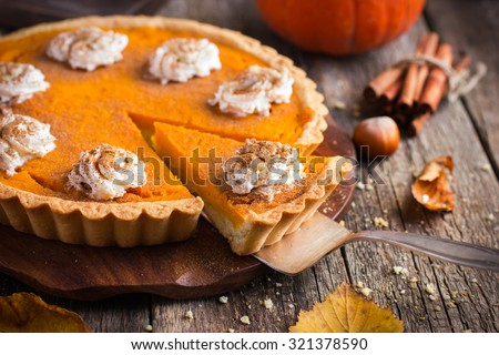 pumpkin pie with whipped cream and cinnamon on rustic background, top view Royalty-Free Stock Photo #321378590