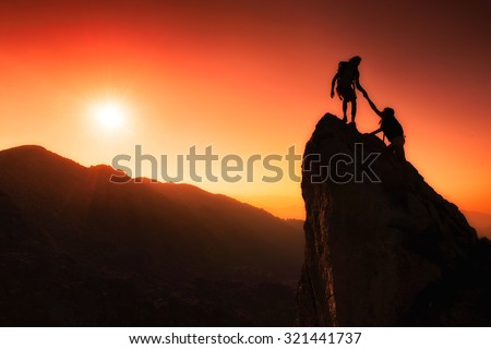 Team of climbers help to conquer the summit in teamwork in a fantastic mountain landscape at sunset #321441737