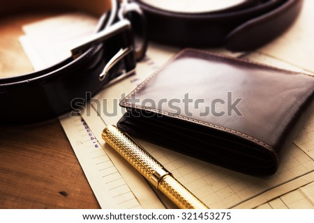Documents, pen, belt and a leather wallet on a wooden desk. hotel table or gentleman's desk. shallow depth of field. Royalty-Free Stock Photo #321453275