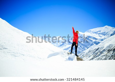 Young happy woman hiker successful on mountain peak summit in winter mountains. Climbing inspiration and motivation beautiful landscape. Fitness healthy lifestyle outdoors on snow in Himalayas, Nepal. #321484145