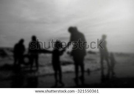 silhouette Family Shadow enjoying the beach Black and white blurred background #321550361