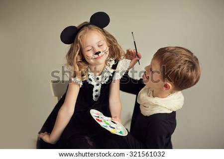 Brother and sister playing at artist and model. Face painting, #321561032