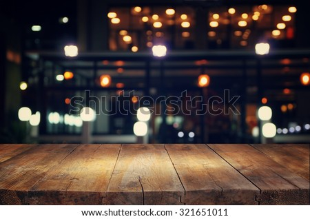 image of wooden table in front of abstract blurred background of resturant lights  Royalty-Free Stock Photo #321651011