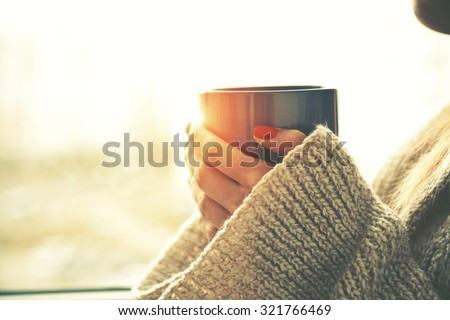 hands holding hot cup of coffee or tea in morning sunlight Royalty-Free Stock Photo #321766469