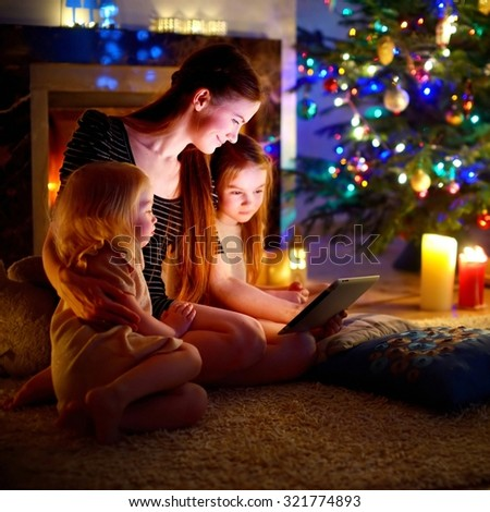 Young mother and her daughters using a tablet pc by a fireplace on warm Christmas evening #321774893