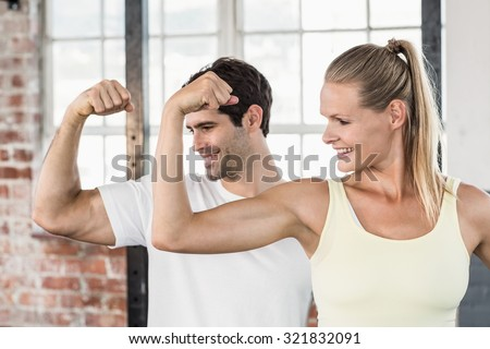 Portrait of couple flexing muscles at the gym #321832091