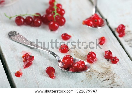 Fresh red currants on wooden table close up #321879947
