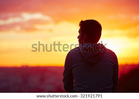 Young man is looking at the sunrise. Royalty-Free Stock Photo #321921791
