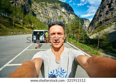 young  man make selfie on the morning mountains background. Man dressed in a white t-shirt and white sunglasses #321951512