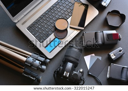 desktop with photography equipment, camera, tripod,flash  and computer #322015247