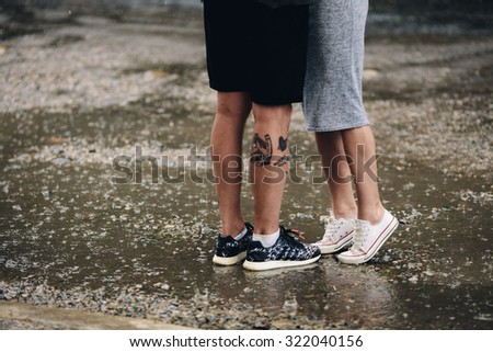 Photo of the lower half of the body on the background of a pair of wet asphalt