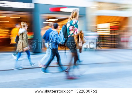 people in motion blur on the move in a shopping street of a city #322080761
