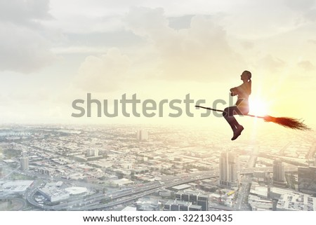 Young girl in casual flying on broom high in sky #322130435